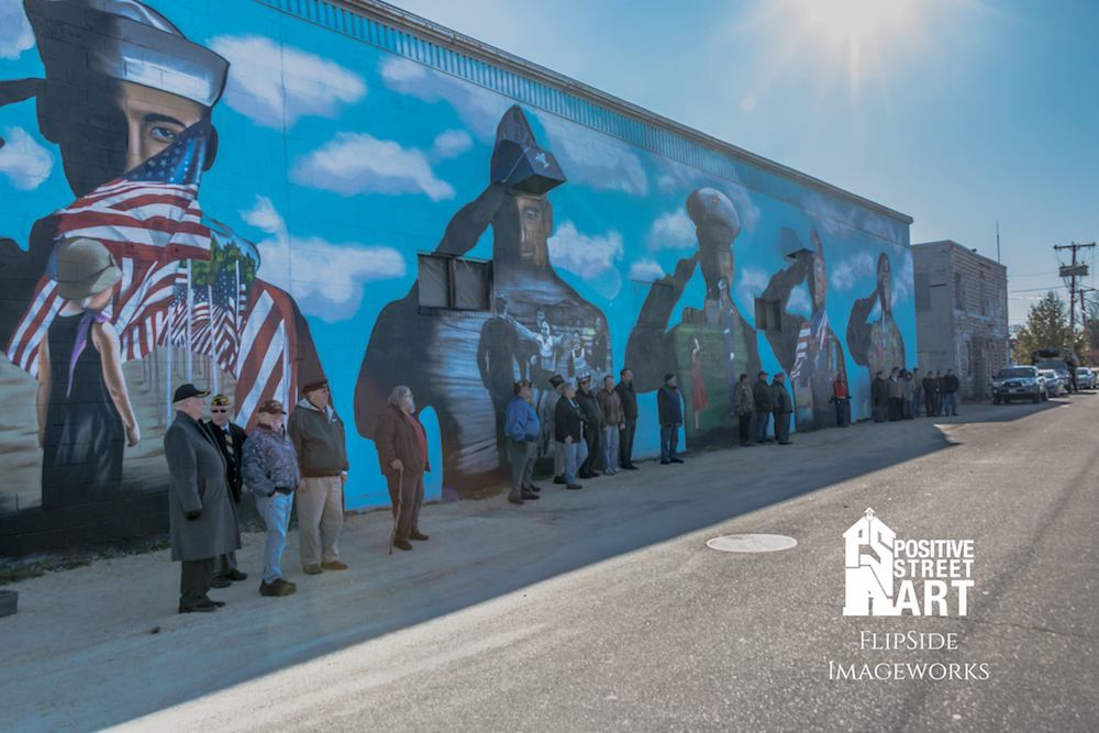 A mural dedication was held on the morning of Veterans Day, 2017 where this above image was taken. It depicts veterans in attendance representing their branch by standing in front of the respective figure